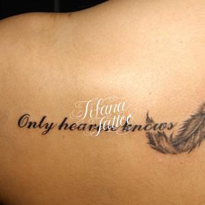 羽と文字のタトゥー