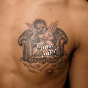 椅子に座る天使のタトゥー