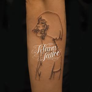 花を咥えた女性の抽象画タトゥー