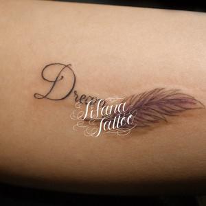 フェザーと文字のタトゥー