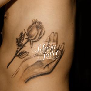 バラに手を添えたタトゥー